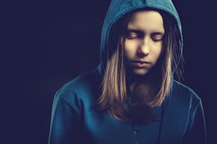 Afraided teen girl in hood, studio shot